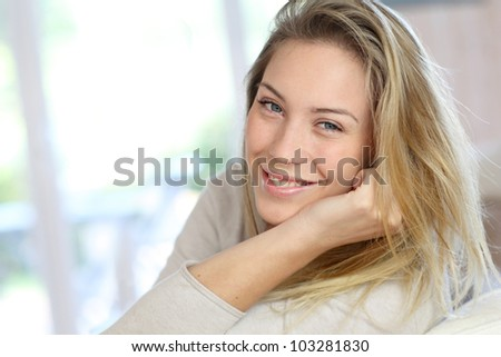 Attractive young blond woman relaxing in sofa