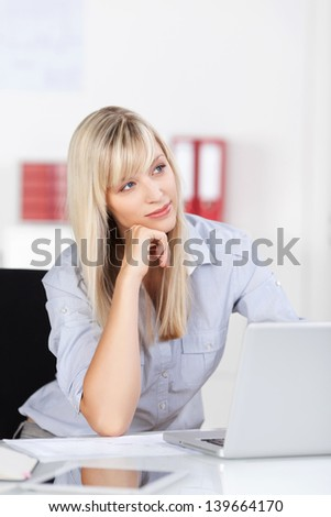 Attractive young blond woman sitting at her laptop staring off into space contemplating her business strategy - stock photo