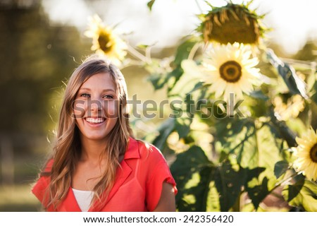 Attractive Young Blond Woman smiling next to sunflowers - stock photo