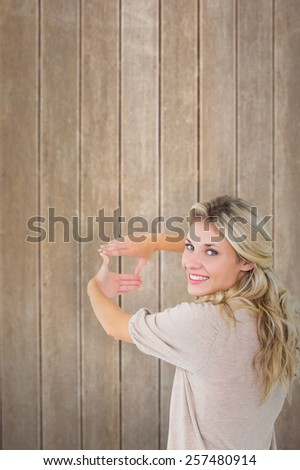 Attractive young blonde framing with her hands against wooden surface with planks - stock photo