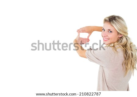 Attractive young blonde framing with her hands on white background