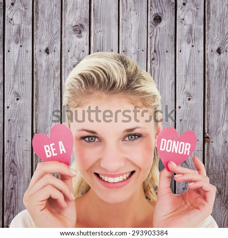 Attractive young blonde holding little hearts against digitally generated grey wooden planks - stock photo