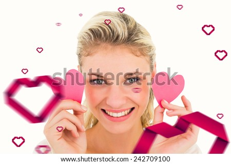 Attractive young blonde holding little hearts against hearts - stock photo