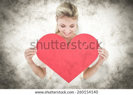 Attractive young blonde showing red heart against grey background - stock photo