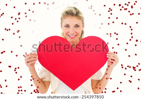 Attractive young blonde showing red heart against red love hearts - stock photo