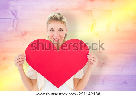 Attractive young blonde showing red heart against yellow and purple planks - stock photo