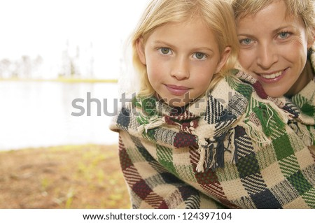 Attractive young blonde sisiter and brother wrapped up in blankets against the cold while down at the lake - stock photo