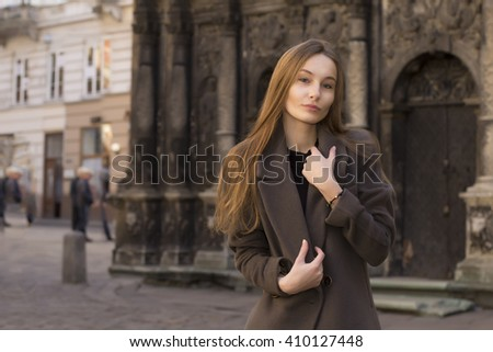 Attractive young blonde woman in a grey coat at the street - stock photo