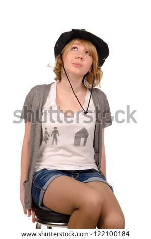 Attractive young blonde woman in a trendy cowboy hat and denim shorts sitting on a stool looking up at the sky as though seeking inspiration - stock photo
