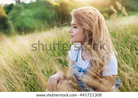 Attractive young blonde woman in the summer park