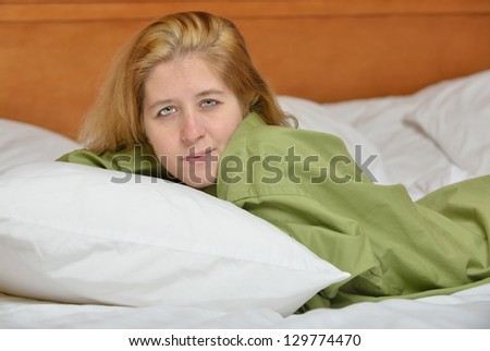 Attractive young blonde woman laying in bed wearing a green men's shirt - stock photo