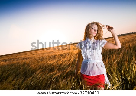 Attractive young blonde woman standing in a wheat - stock photo