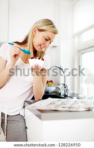 Attractive young blonde woman standing reading the newspaper at the kitchen counter while enjoying her breakfast - stock photo