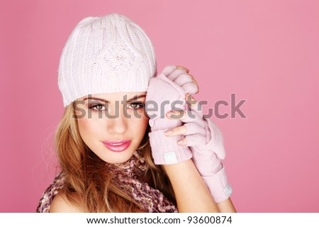 Attractive young blonde woman wearing winter outfit, head and shoulders portrait on pink. - stock photo