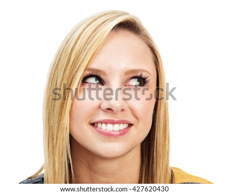Attractive young blonde woman with a mischievous look on her face, looking away to one side