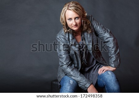 Attractive young blonde woman with attitude looking at camera in studio - stock photo