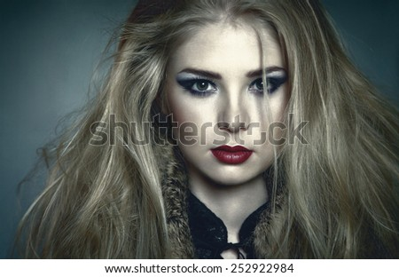 Attractive young blonde woman with long disheveled hair looking at camera - stock photo