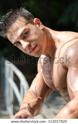 Attractive young bodybuilder outdoors, leaning on metal railing