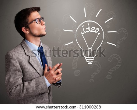 Attractive young boy comming up with a light bulb idea sign - stock photo