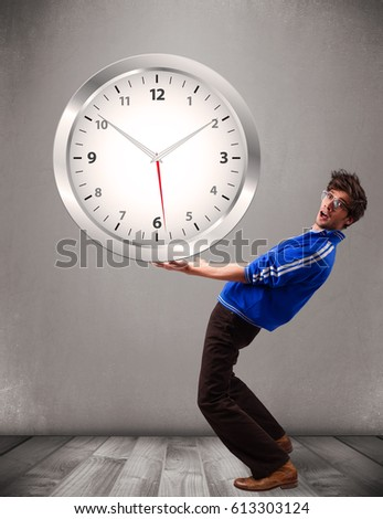 Attractive young boy holding a huge clock