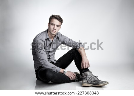 Attractive, young boy is sitting on the floor - stock photo