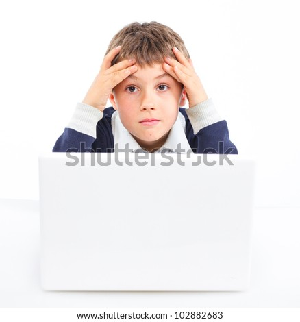 Attractive young boy using notebook computer. Isolated on white background.