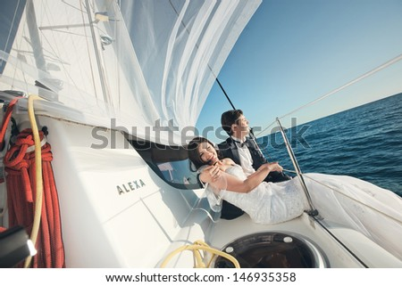 Attractive young bride and groom in wedding dress laughs on a yacht at a sunny summer day  - stock photo