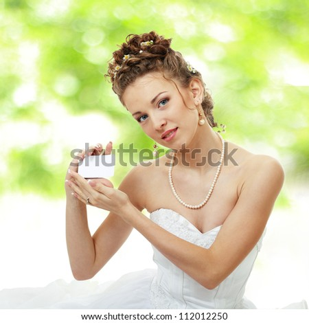 Attractive young bride holds out empty business card or creditcard outdoor soft summer background - stock photo