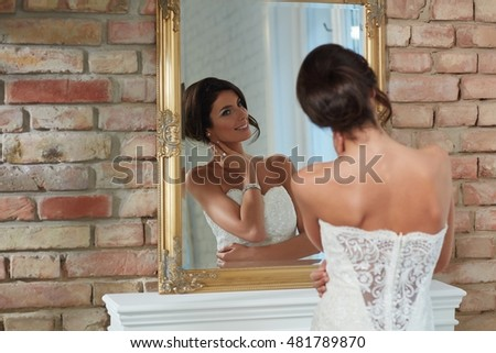 Attractive young bride looking at herself in mirror, posing.