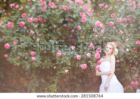 Attractive young bride posing near roses garden - stock photo