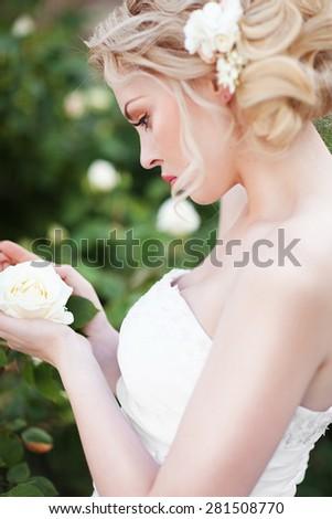 Attractive young bride posing near roses garden - stock photo