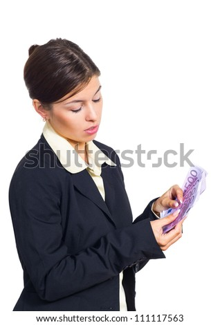 Attractive young brunette businesswoman holding in her hands a stack of banknotes euro and counts the money. Isolated against white background.