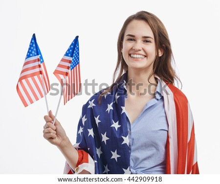 Attractive young brunette girl celebrating National Independence Day on 4th of July in United States of America. Pretty model with cheerful toothy smile on isolated white background - stock photo