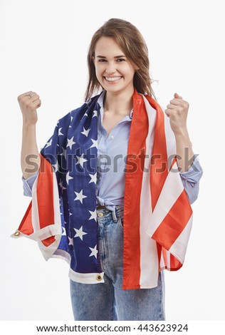 Attractive young brunette girl covered by National Flag celebrating Independence Day on 4th of July in United States of America.Emotional model with toothy smile on isolated white background - stock photo