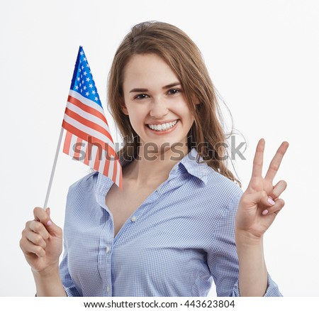 Attractive young brunette girl holding National Flag celebrating Independence Day on 4th of July in United States of Ameica.Emotional model showing peace gesture.Isolated background - stock photo