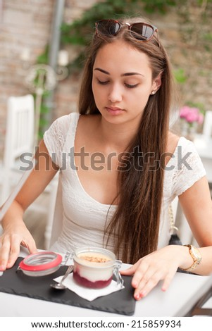 Attractive young brunette having dinner in a fancy restaurant. - stock photo