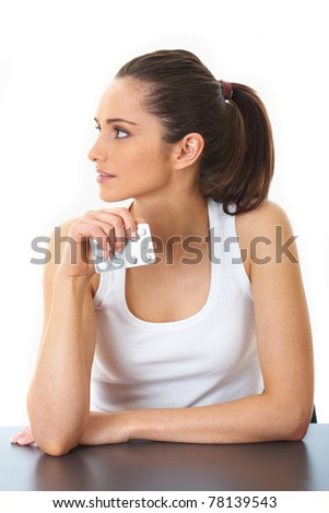 attractive young brunette holds some pills in her hand, isolated on white - stock photo