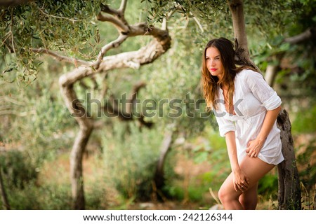 Attractive, young brunette on the beach, amid olive trees, looking both sensual and natural - stock photo