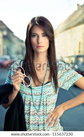 Attractive young brunette posing on the street. Fashion concept. - stock photo