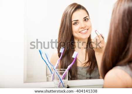 Attractive young brunette putting some lipstick on while standing in front of a bathroom mirror and making eye contact - stock photo