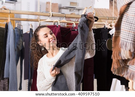 Attractive young brunette selecting new breeches at the store 