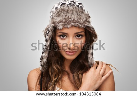 Attractive young brunette smiling on grey background - stock photo