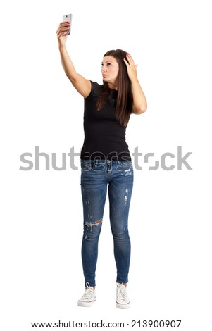 Attractive young brunette taking high angle self photo or selfie with her smart phone.  Full body length isolated over white.