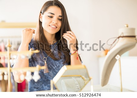 Attractive young brunette trying on a necklace in front of a mirror at a jewelry shop