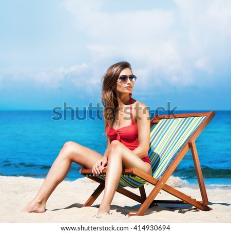 Attractive, young brunette with hot legs wearing glasses and alluring swimwear sitting in the deckchair on the beach.