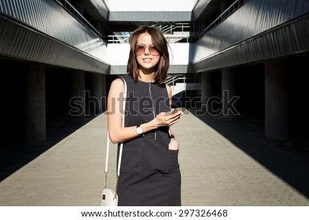 Attractive young brunette woman checking new messages, holding mobile phone in her hand and standing outdoors in the city parking area on a bright sunny day