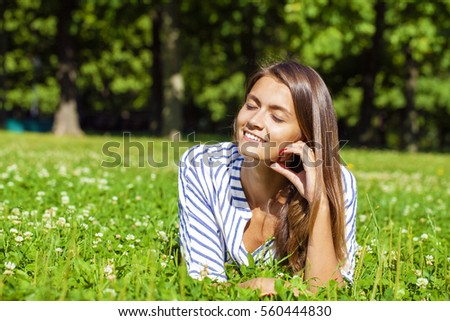 Attractive young brunette woman lying on green grass field at summer park