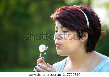 Attractive young brunette woman under soft natural lighting blowing on a dried dandelion. Shallow depth of field. - stock photo