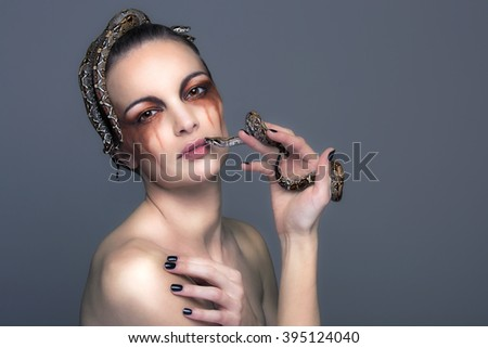 Attractive young brunette woman with boa constrictor - snake