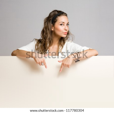 Attractive young brunette woman with large blank billboard. - stock photo